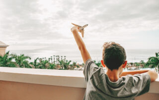 rear view boy holding plane toy dreaming about travel