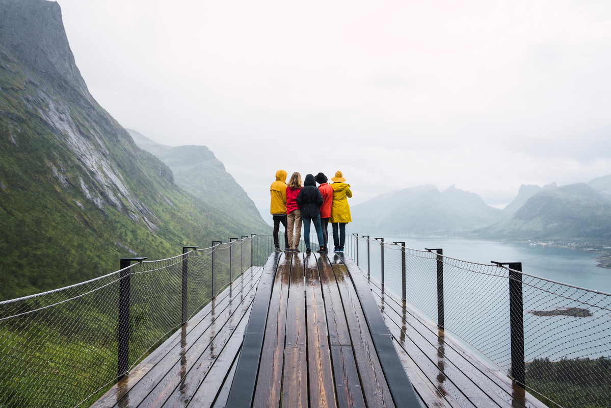 Norway, Senja island, rear view of friends standing on an observation deck at the coast