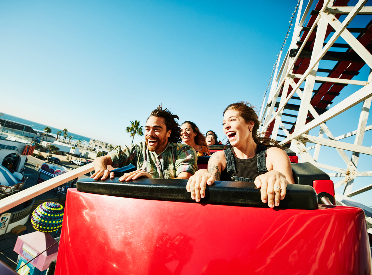 Laughing and screaming couple riding roller coaster at amusement park
